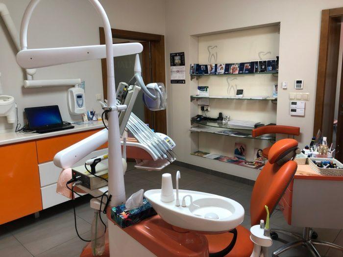 Fotel dentystyczny, wtle półka zobrazkami iaparatura dentystyczna