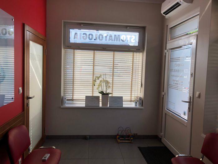 Po prawej widoczne drzwi wejściowe dobudynku, naśrodku okno znapisem Stomatologia powyżej