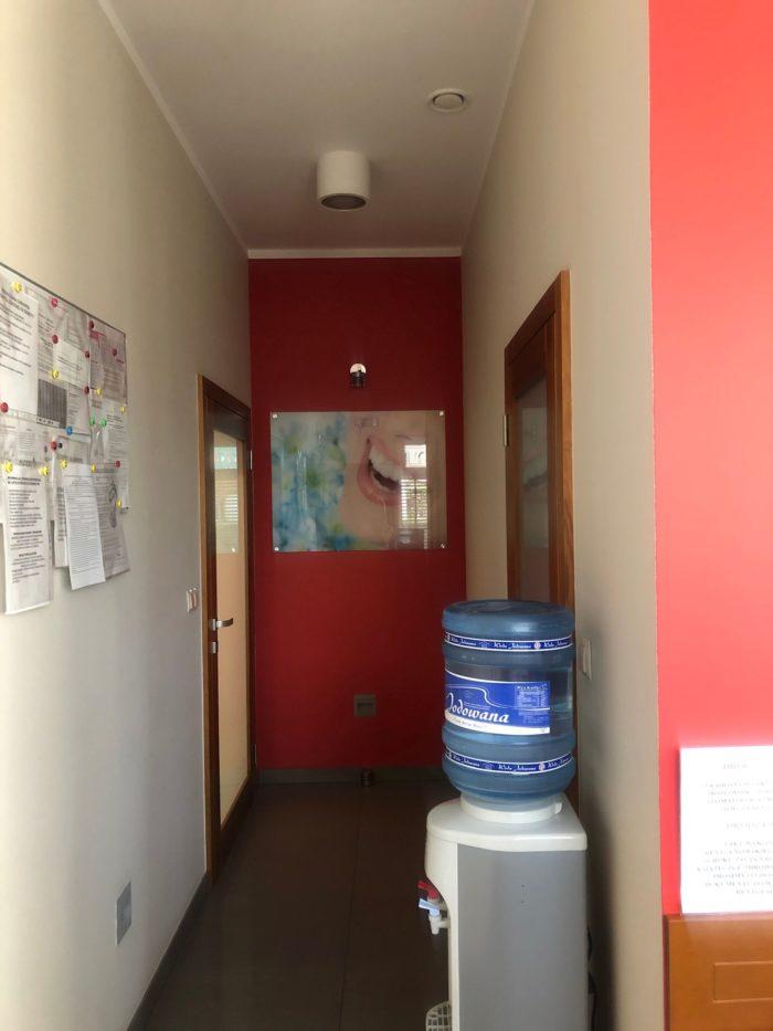 Widok korytarza zestojącym automatem dowody orazdrzwiami poobu stronach